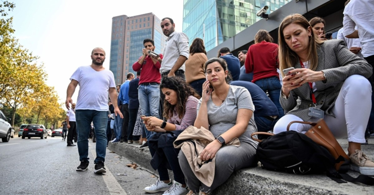Office workers speak on their phones after fleeing their buildings in the Maslak District of Istanbul on Sept. 26, 2019, after an earthquake struck the city. (AFP Photo)