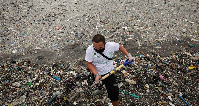 A Filipino volunteer shovels garbage from the banks during a cleanup at the Manila Bay in Manila, Philippines, Aug 20, 2016. (EPA Photo)