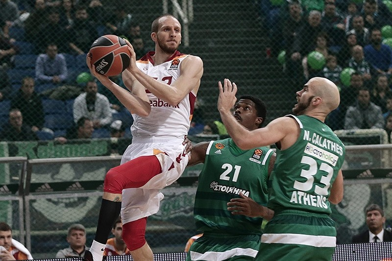 Galatasaray's shooting guard Sinan Gu00fcler (L) throws the ball past Panathinaikos point guard Nick Calathes (33) during the Euroleague 11th week game, in Athens, on Dec. 10, 2016. (AA Photo)