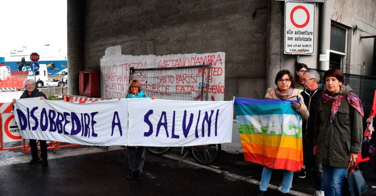 Activists holds up a sign with writing reading in Italian ,Disobey Salvini,as they demonstrate after Saudi Arabian freighter Bahri Yambu docked in Genoa's port, Italy, Monday, May 20, 2019 (AP Photo)