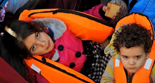 Two migrant children wait at the Çeşme port after they were brought there by the Coast Guard.