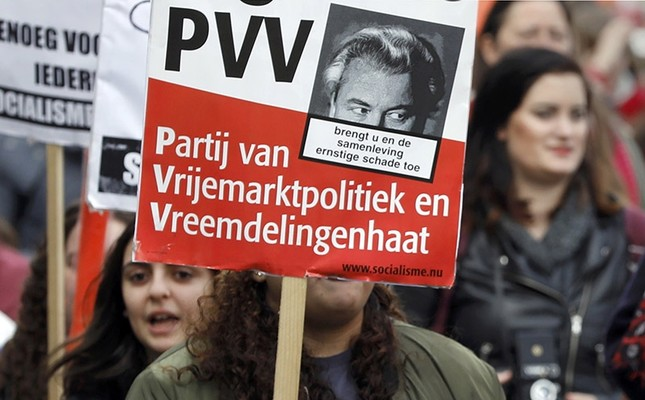 A demonstrator carries a sign reading PVV - The party of free market policy and xenophobia , during a march in Amsterdam, Netherlands, March 11, 2017. (Reuters Photo)