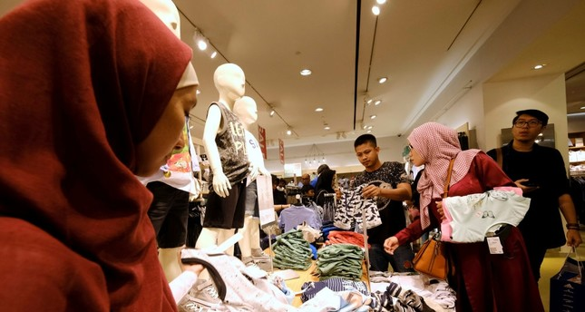 Customers hold clothes during late night Ramadan shopping at Gandaria Mall in Jakarta, Indonesia.