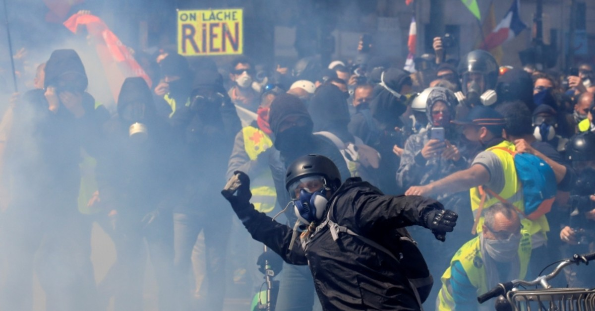 Tear gas floats around masked protesters during clashes before the start of the traditional May Day labour union march in Paris, France, May 1, 2019.  (Reuters Photo)