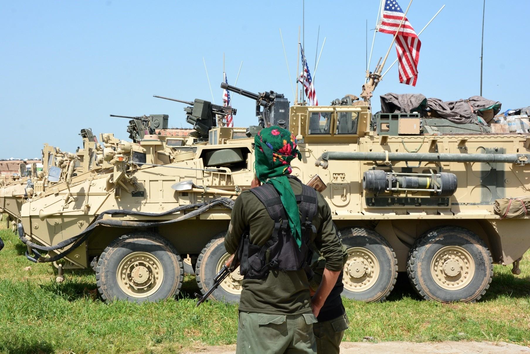 YPG terrorists stand next to U.S. eight-wheeled armored vehicles, near al-Ghanamya, al-Darbasiyah at the Syrian-Turkish border, April 29.