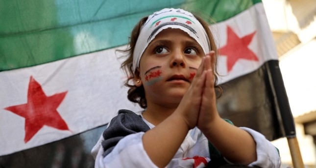 A Syrian girl claps as she takes part in a protest against the regime in the town of Kafr Takharim Syria's northwestern Idlib governorate on Sept. 27, 2019. (AP Photo)