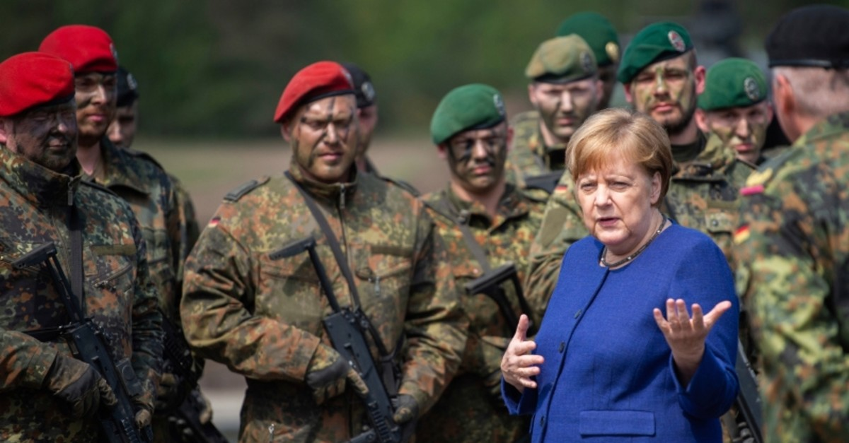 German Chancellor Angela Merkel, right, talks to soldiers of the Very High Readiness Joint Task Force (VJTF) after an exercise in Munster, Germany, Monday, May 20, 2019. (dpa via AP)