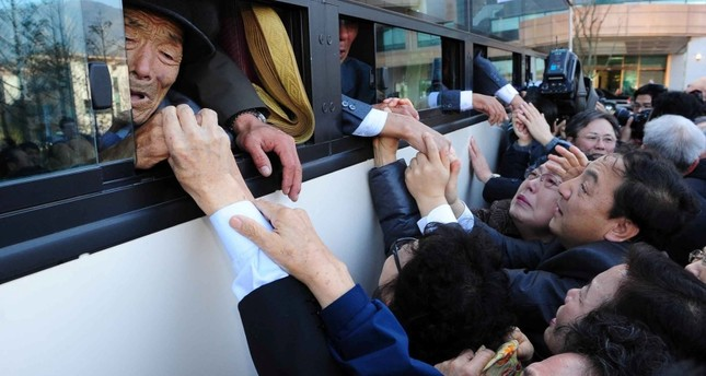 In a file picture taken on November 1, 2010 North Koreans (in the bus) grip hands of their South Korean relatives as they bid farewell following their family reunion meeting at North's Mount Kumgang resort, near the border. (AFP Photo)