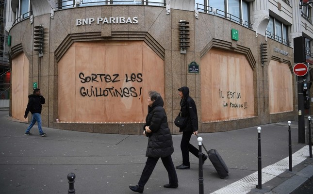 People walk past the protective wooden walls on a bank with a tag Get the guillotines out and money is here on Boulevard des Capucines in Paris, Dec. 9.