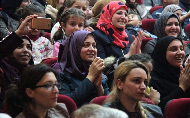 Syrian refugees sing along as the choir sings on stage.