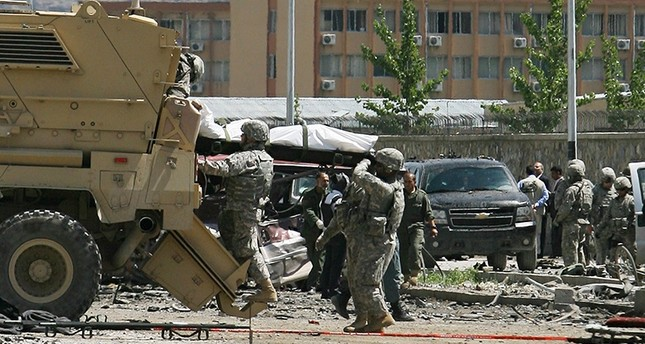 In this May 18, 2010 file photo, U.S. soldiers load dead bodies on a vehicle after a suicide attack in Kabul, Afghanistan. (AP Photo)