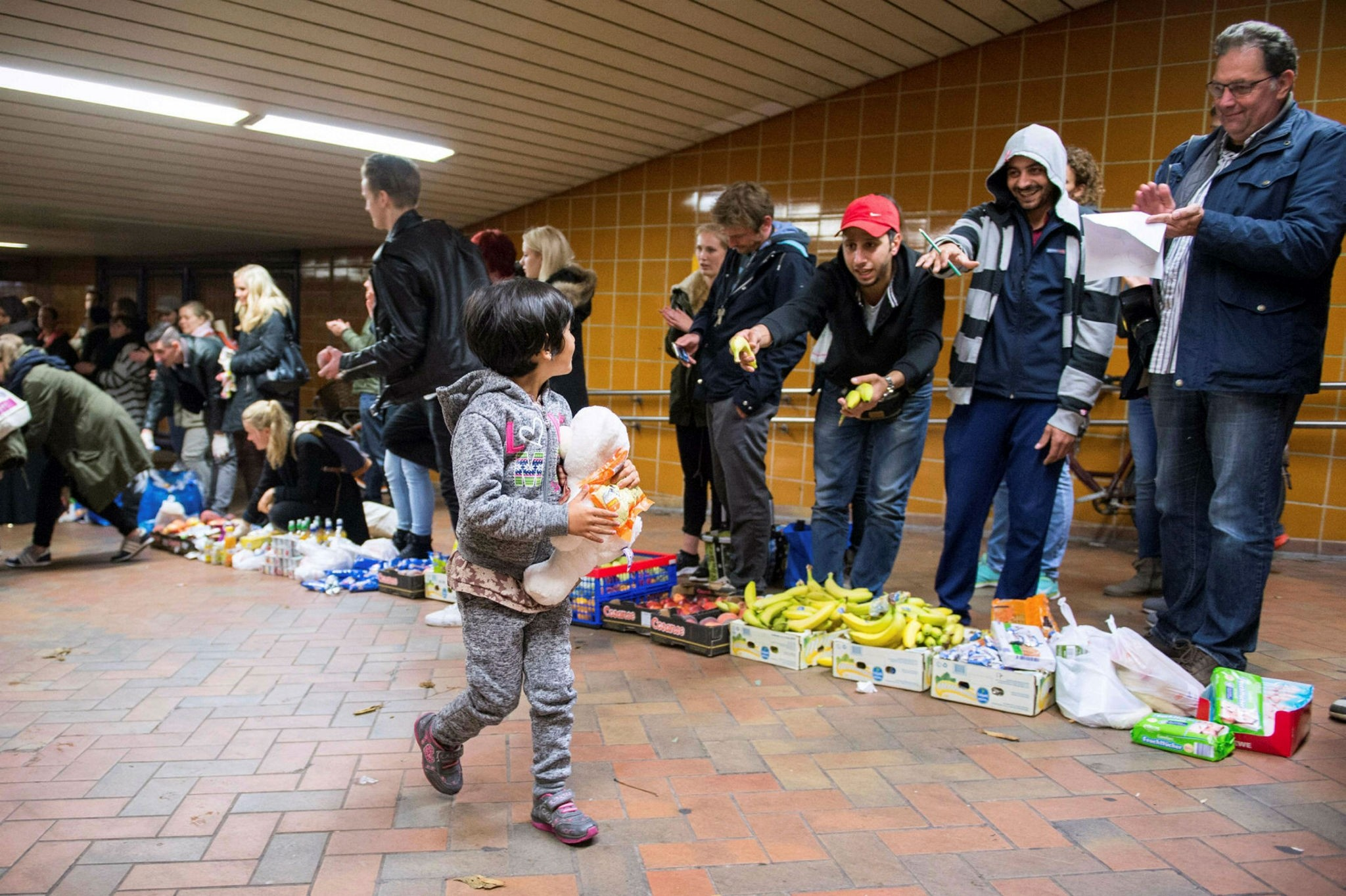 A migrant girl walks past volunteers who distribute food and drinks to migrants after their arrival at the railway station of Hamburg.