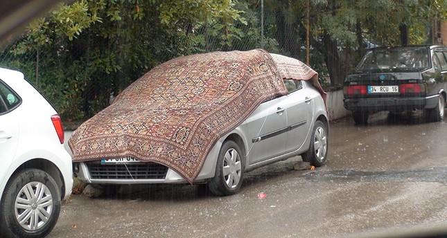 غطى المواطنون سياراتهم تحسباً من هطول حبات البَرَد (الأناضول)