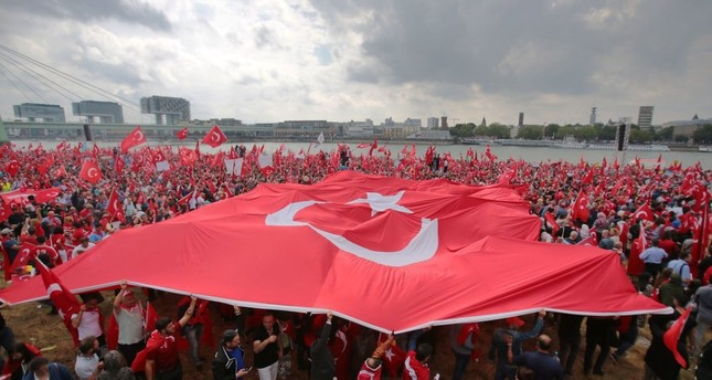 People waving  flags at a pro-democracy rally against the failed coup attempt, Cologne, Germany, July 31.