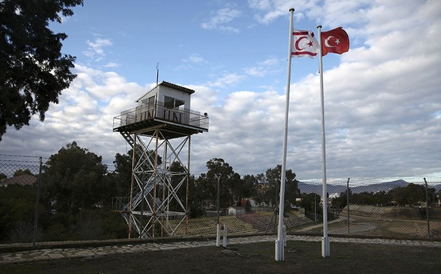 A UN guard post is seen on the buffer zone as a Turkish and a Turkish Cypriot flag wave on the part of the divided city of Nicosia, TRNC, January 12, 2017. (Reuters Photo)