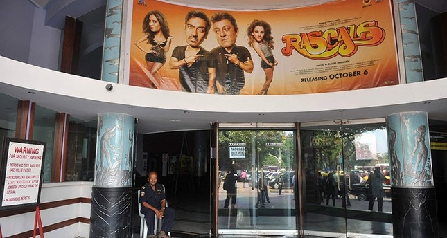 A movie theatre hall watchman sits at the Eros theatre in Mumbai, 7 October 2011. (AFP Photo)