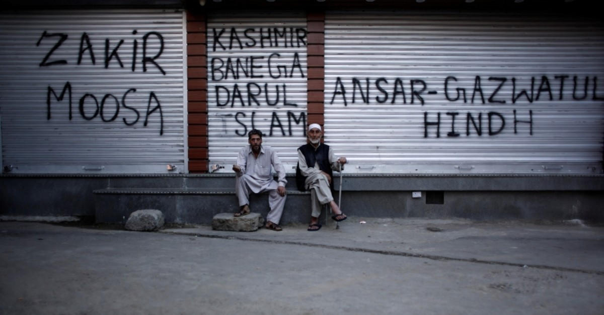 Kashmiri men sit in front of the closed shops painted with graffiti during restrictions after scrapping of the special constitutional status for Kashmir by the Indian government, in Srinagar, Aug. 20, 2019. (Reuters Photo)