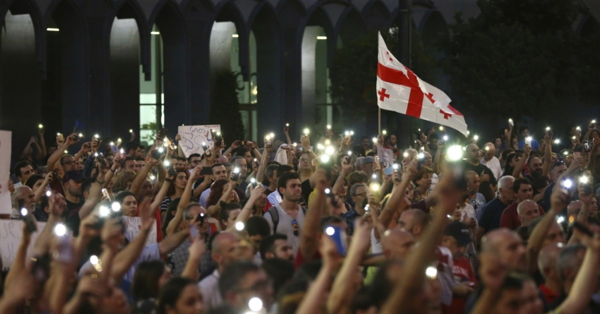 Opposition demonstrators with a Georgian national flag gather outside the Georgian Parliament building in Tbilisi, Georgia, June 23, 2019.