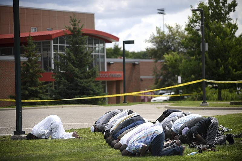Mohamed Omar, left, the executive director of the Dar Al Farooq Center Islamic Center leads afternoon prayers outside the police tape surrounding the center Saturday Aug. 5, 2017 (AP Photo)