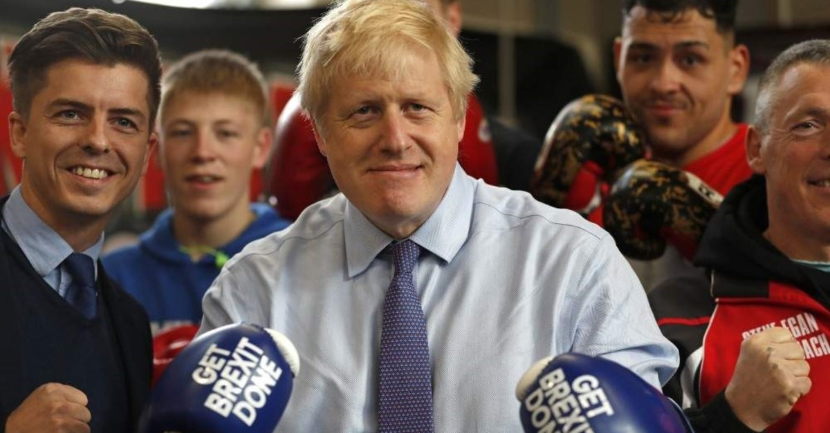 Britain's Prime Minister Boris Johnson poses for a photo wearing boxing gloves during a stop on his general election campaign trail, Manchester, Nov. 19, 2019. (AP Photo)