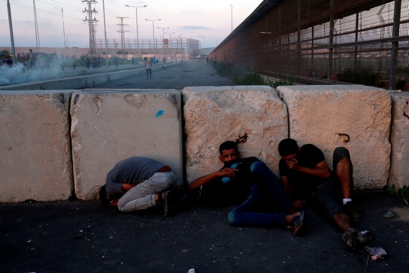 Palestinian protestors take cover during a demonstration at the Erez crossing with Israel on September 18, 2018, in the northern Gaza Strip. (AFP Photo)