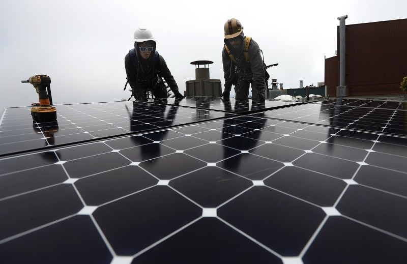 Luminalt solar installers Pam Quan (L) and Walter Morales (R) install solar panels on the roof of a home on May 9, 2018 in San Francisco, California. (AFP Photo)