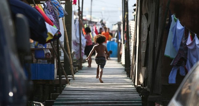 In this Nov. 15, 2018, file photo, a girl runs towards their home at Port Moresby, Papua New Guinea (AP File Photo)