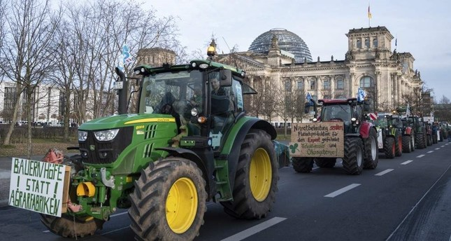 Farmers drive past the Reichstag building with their tractors in Berlin, Saturday, Jan.18, 2020. AP Photo