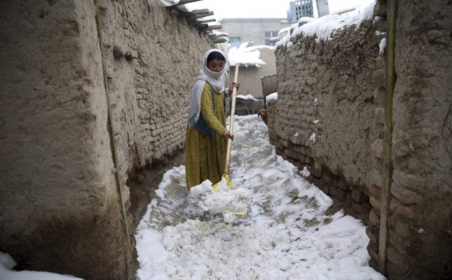 An internally displaced young Afghan woman cleans an alley outside her house on the outskirts of Kabul, Afghanistan, Sunday, Jan. 12, 2020. AP Photo