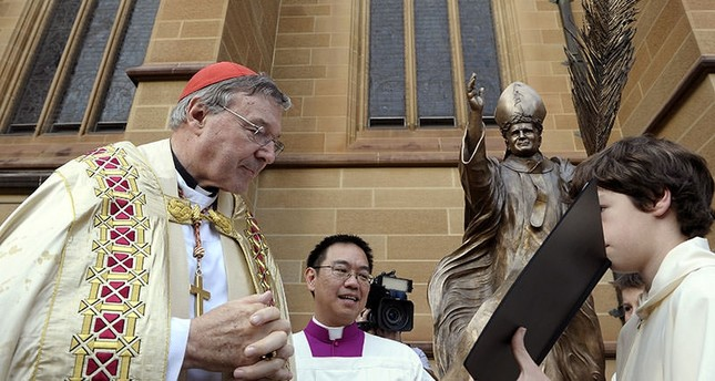 FILE - In this May 1, 2011 file photo, Cardinal George Pell, left, reads a bible during the blessing of a statue of John Paul ll at St Mary's Cathedral in Sydney, Australia. (AP Photo)