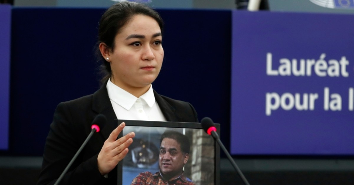 Jewher Ilham, daughter of imprisoned Uighur scholar Ilham Tohti holds a photo of her father during the Sakharov Prize ceremony at the European Parliament, in Strasbourg, eastern France, Wednesday, Dec. 18, 2019. (AP Photo)