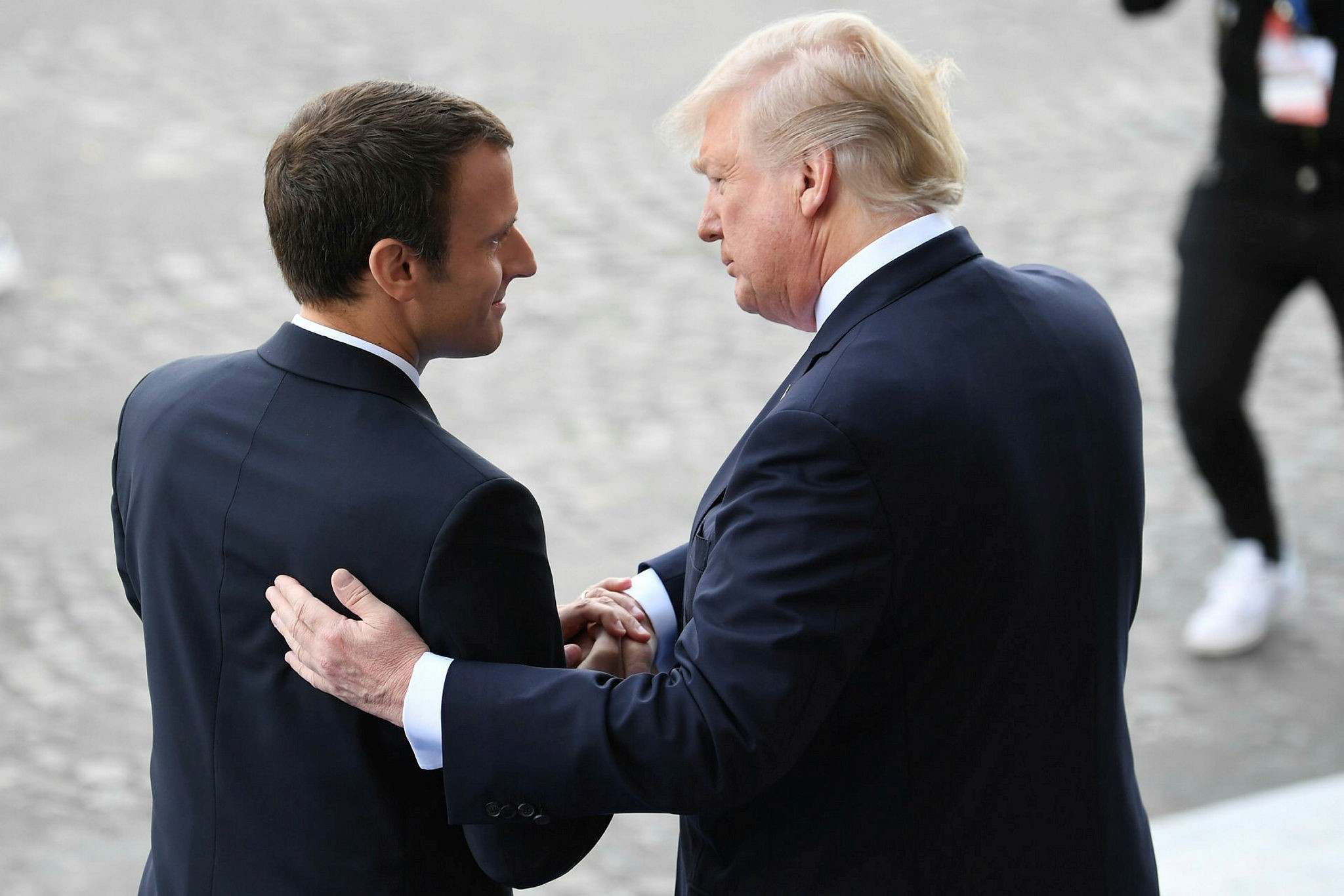 In this file photo taken on July 14, 2017 French President Emmanuel Macron (L) bids farewell to his US counterpart Donald Trump after the annual Bastille Day military parade on the Champs-Elysees avenue in Paris. (AFP Photo)