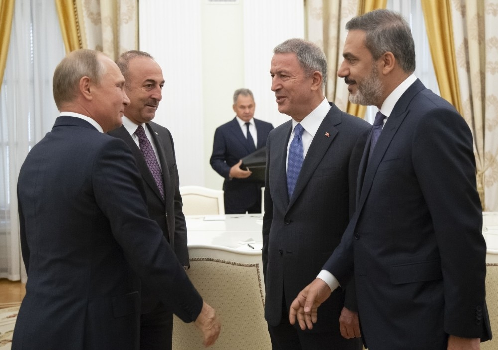 (From left to right) Russian President Vladimir Putin, Foreign Minister Mevlu00fct u00c7avuu015fou011flu, Defense Minister Hulusi Akar and intelligence chief Hakan Fidan talk to each other during their meeting in the Kremlin, Moscow, Aug. 24.