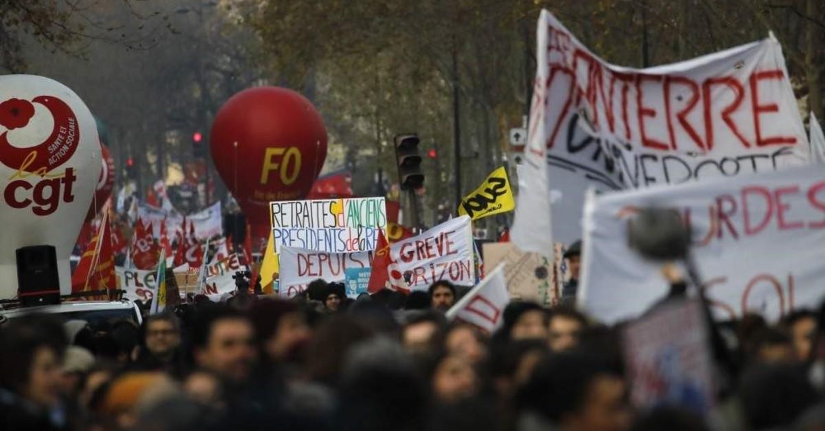 People march during a demonstration, Paris, Dec. 10, 2019. (AP Photo)