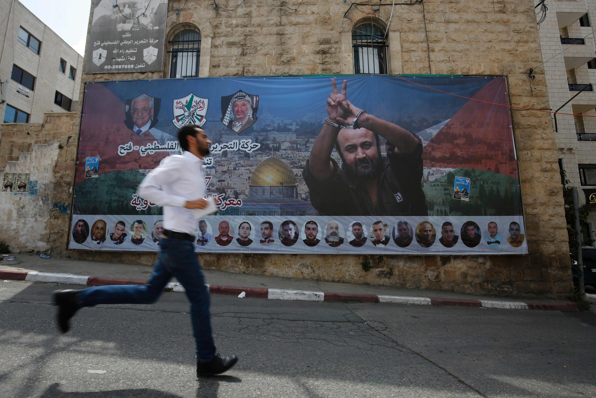 A Palestinian runs past a poster bearing a portrait of Palestinian leader Marwan Barghouti in the West Bank city of Ramallah on May 3, 2017. (AFP PHOTO)