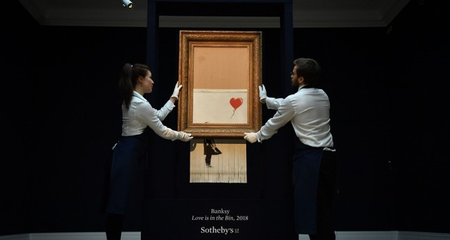 Sotheby's employees pose with the newly completed work by artist Banksy entitled Love is in the Bin at Sotheby's auction house in London on October 12, 2018. (AFP Photo)