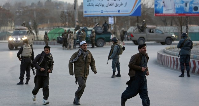 People run away from the site of a clash between insurgents and security forces in Kabul, Afghanistan, Monday, Dec. 24, 2018 (AP Photo)