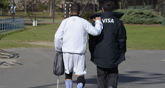 Argentine paralympic blind football forward Silvio Velo (L) walks assited by Boca Juniors blind football coach Mariano Arnal before a training session in Buenos Aires on May 19, 2016, ahead of the Rio 2016 Paralympic Games. (AFP Photo)