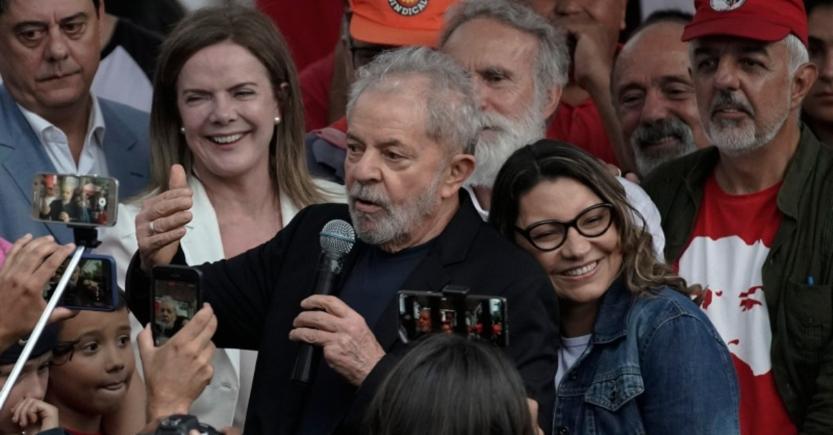 Brazil's ex-President Luiz Inacio Lula da Silva speaks as his girlfriend Rosangela da Silva leans on his back after he exited the Federal Police headquarters where he was imprisoned on corruption charges in Curitiba, Brazil, Nov. 8, 2019. (AP Photo)