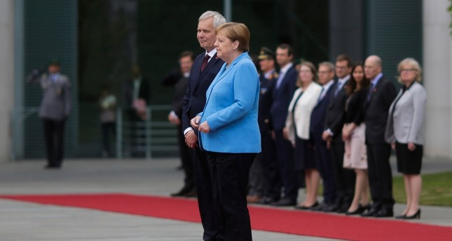 German Chancellor Angela Merkel and Prime Minister of Finland Antti Rinne listen to the national anthems at the chancellery in Berlin, Germany, Wednesday, July 10, 2019. (AP Photo)