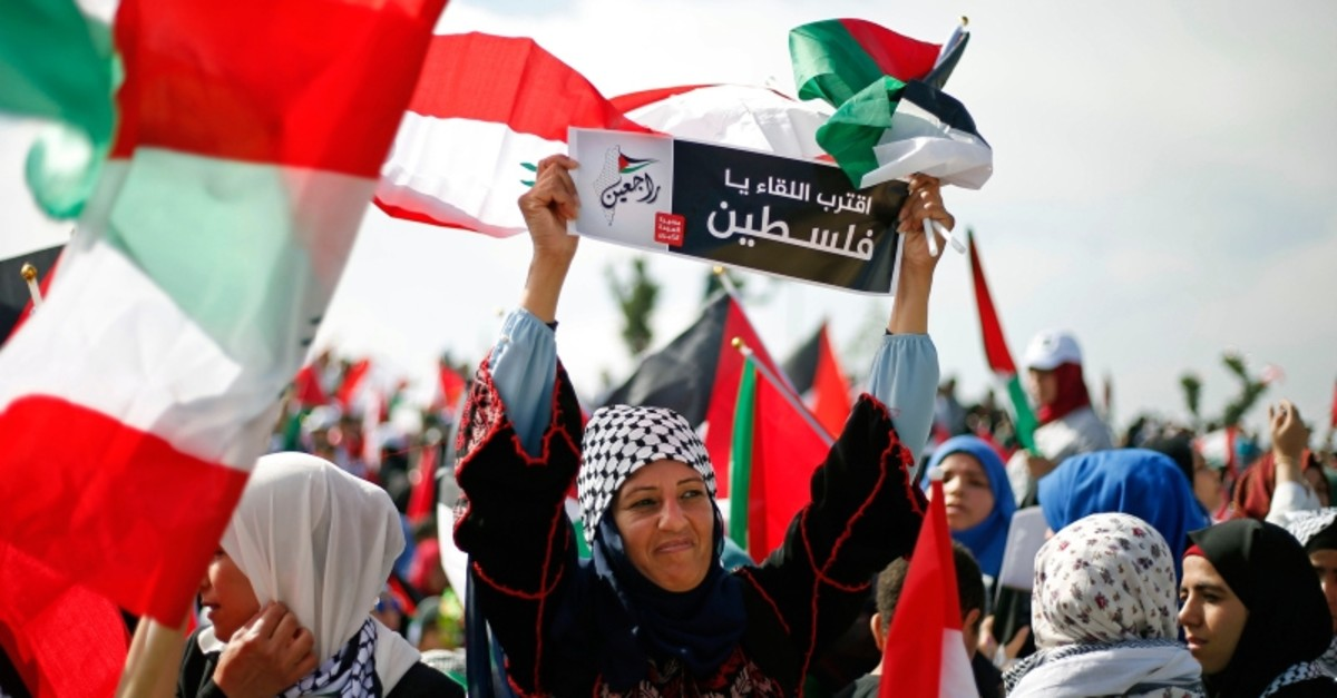 A Palestinian woman living in Lebanon holds a placard with Arabic that reads, ,We will meet soon Palestine, we will return,, during a rally to mark the 70th anniversary of what Palestinians call their ,nakba, (AP File Photo)