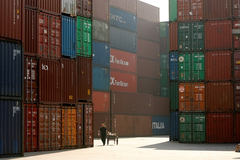 A woman walks past containers at a port in Shanghai, January 13, 2009. (Reuters Photo)