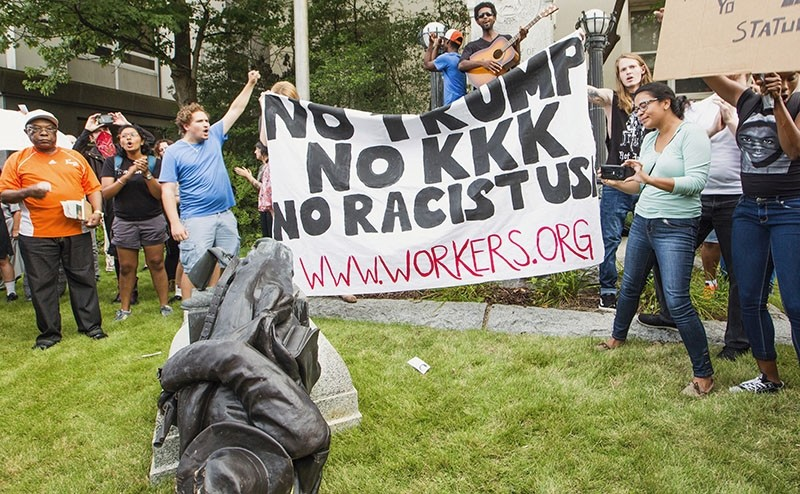 Protesters celebrate after toppling a statue of a Confederate solder in Durham, N.C. Monday, Aug. 14, 2017. (AP Photo)