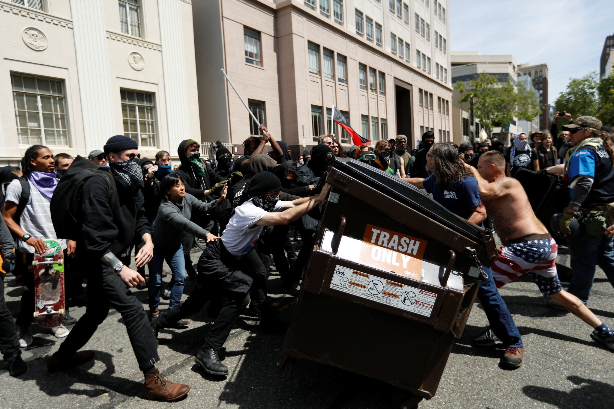 Demonstrators for (R) and against (L) Trump push a garbage container toward each other during a rally in California, U.S., April 15, 2017. (REUTERS Photo)
