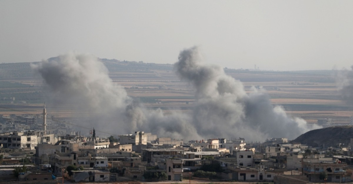 This picture taken on Aug. 5, 2019, shows smoke billowing above buildings during a reported air strike by pro-regime forces on Khan Sheikhun in the south of the northwestern Syrian province of Idlib. (AFP Photo)