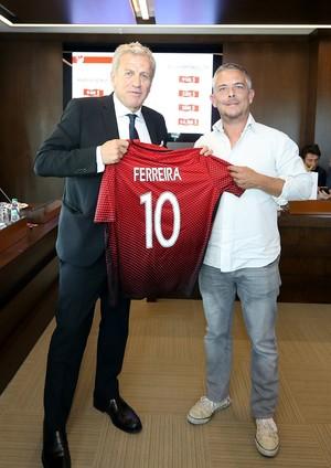 Servet Yardımcı presents a custom made jersey to a foreign journalist.