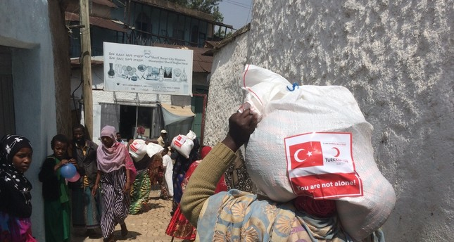 A woman in Ethiopia's Harar carries a food package donated by the Turkish Red Crescent.