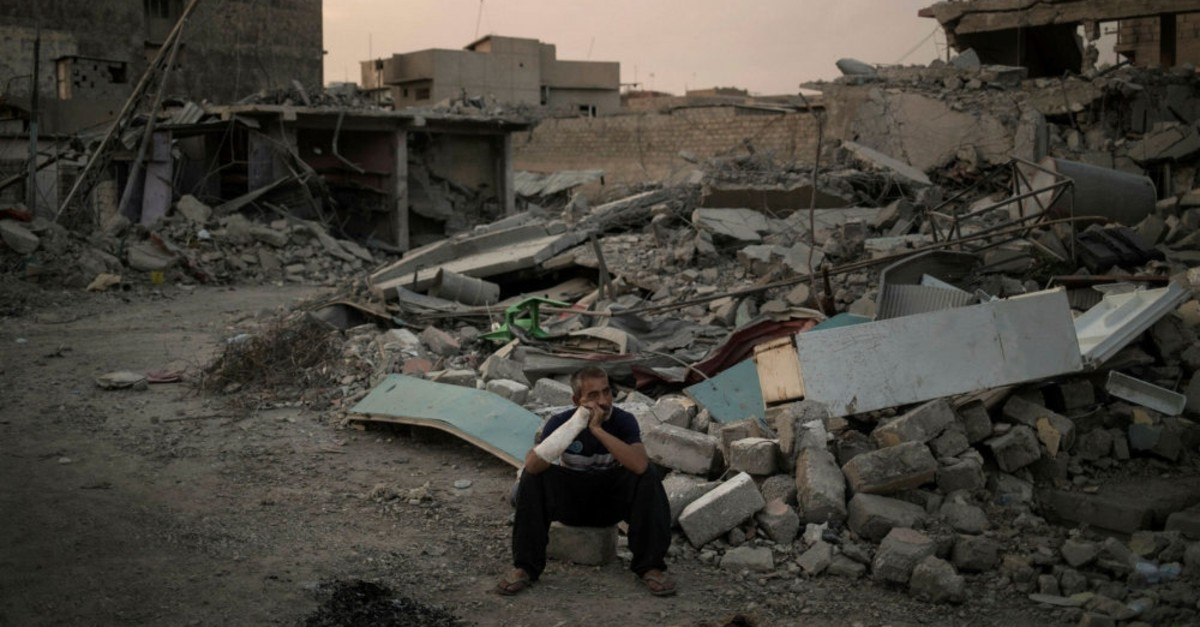 An Iraqi man, who was injured when his house was hit by an explosion, sits on his damaged street on the west side of Mosul, Iraq, July 13, 2017.