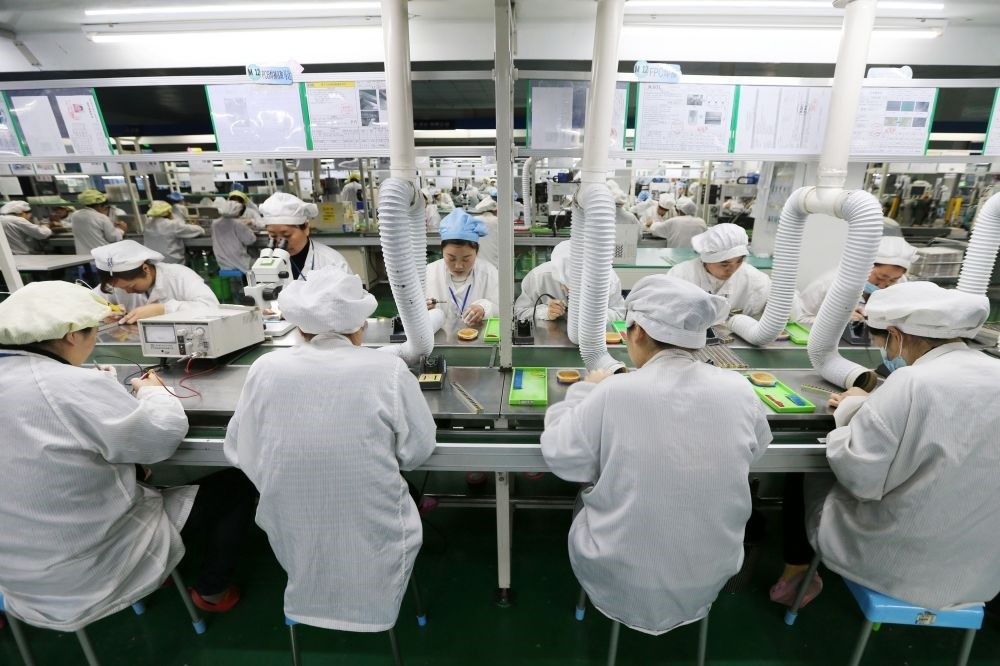 Chinese employees working on micro and special batteries for mobile phones at a factory.