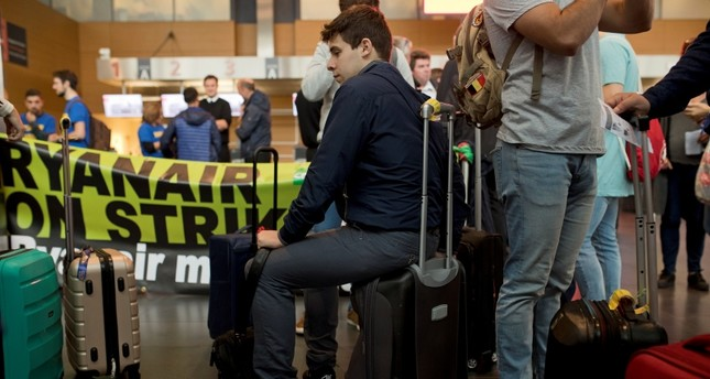 Spanish passengers wait for their flight to Malaga, Spain, in front of Ryanair airline check-in desks during a Ryanair employees strike at the Charleroi airport, outside Brussels, Belgium, Friday, Sept. 28, 2018. (AP Photo)